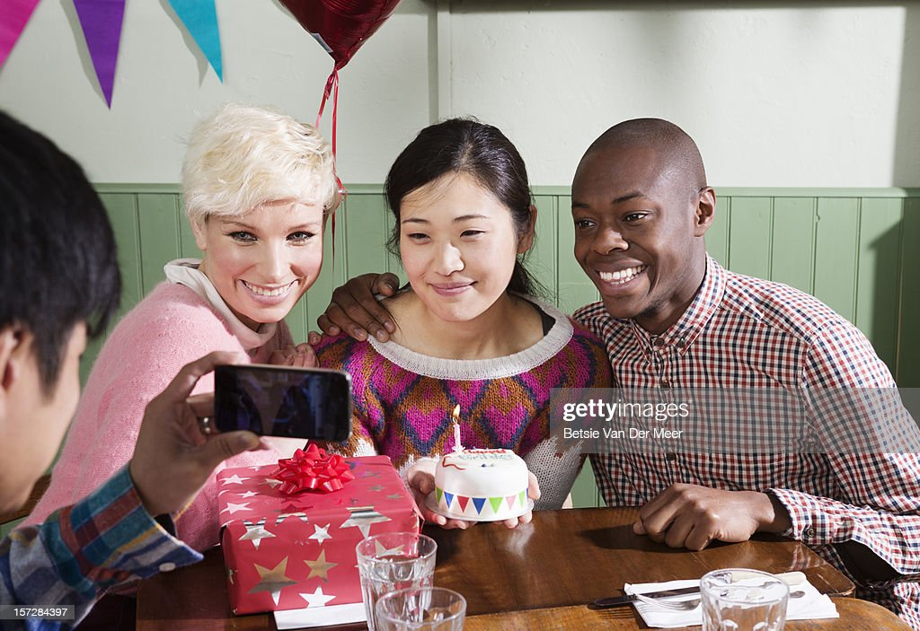 Man taking photo on mobile phone of friends. : Stock Photo
