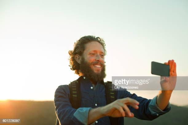 Man taking photograph at the end of a hike