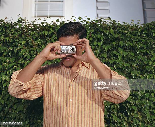 Man taking photograph by hedge