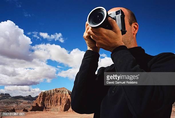 Man taking photograph in desert