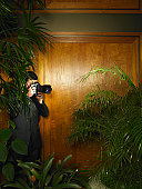Man taking photograph in shadowy building interior