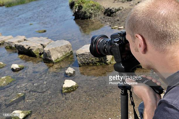 A man taking photographs of a lake using a Canon EOS 40D digital SLR camera During a shoot for PhotoPlus Magazine at Ogmore Castle June 21 2010