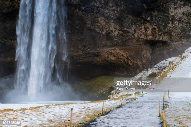 Man taking photos in Seljalandsfoss, Iceland