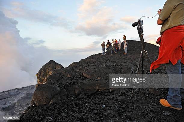 Man taking photos of lava flowing into ocean and steam, Kilauea Volcano, Big Island, Hawaii Islands, USA