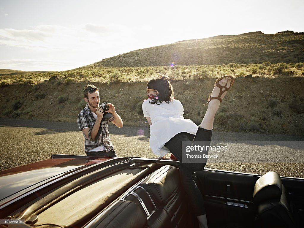 Man taking photos of woman in convertible : Stock Photo