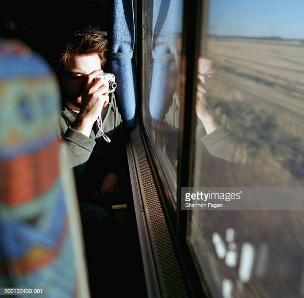 Man taking picture from window