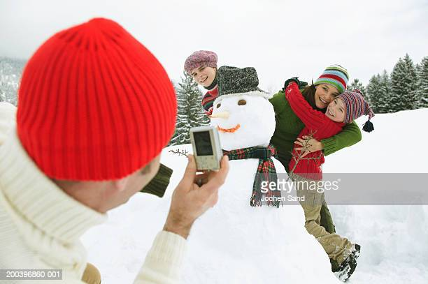 Man taking picture of family by snowman with digital camera
