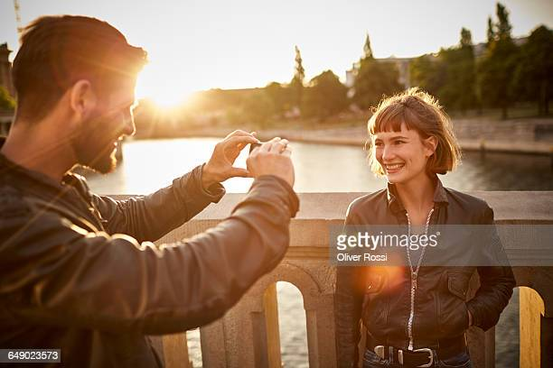 Man taking picture of girlfriend by the riverside
