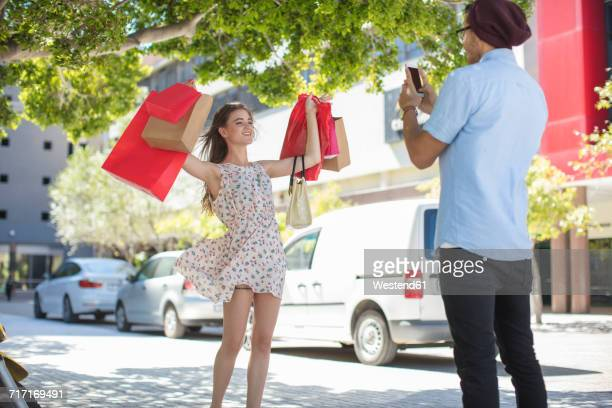Man taking picture of happy young woman with shopping bags