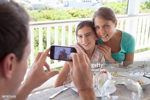 Man taking picture of mother and daughter