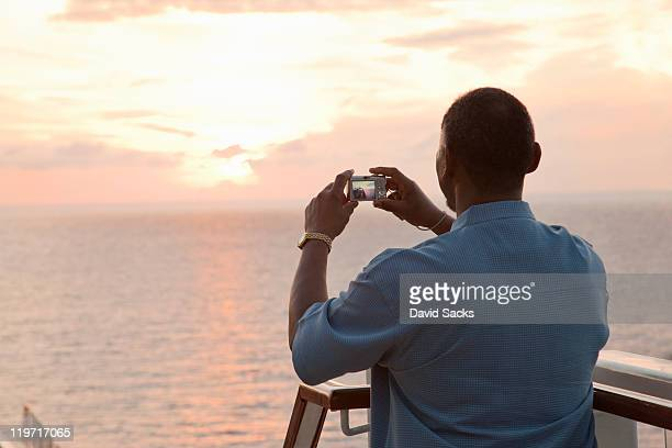 Man taking picture of sunset