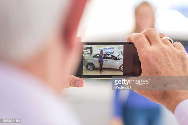 Man taking picture of woman at a new car in showroom
