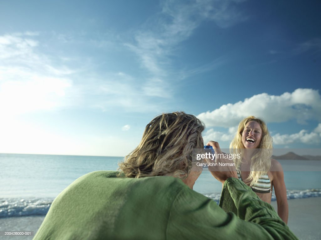 Man taking picture of woman on beach, smiling, close-up