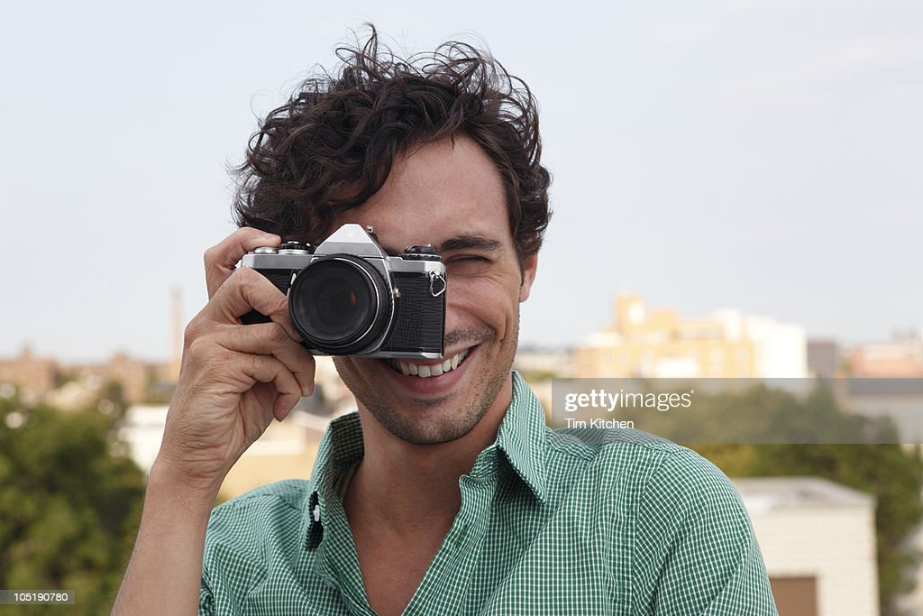 Man taking picture, smiling : Stock Photo
