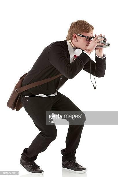 Hombre tomando imagen con una cámara de polaroid