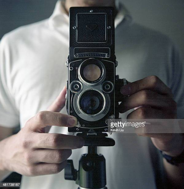 Man taking picture with a vintage camera on tripod