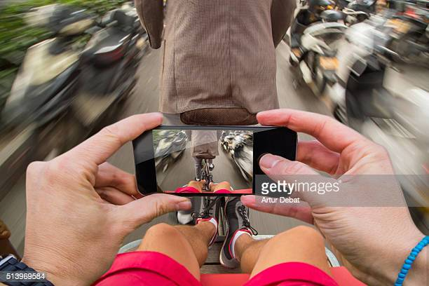 Man taking pictures from personal point of view with smartphone during a commuting with rickshaw in Chinese town.
