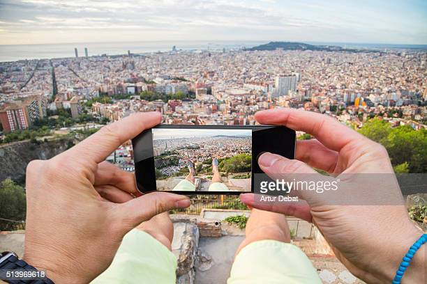 Man taking pictures from personal point of view with smartphone from the Turo de la Rovira hill with the Barcelona cityscape.