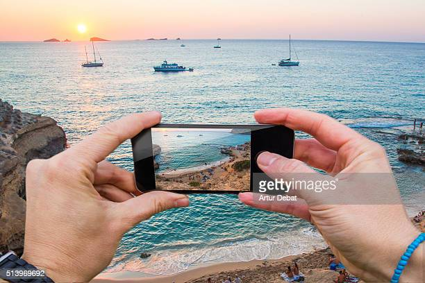 Man taking pictures from personal point of view with smartphone of the Eivissa ( Ibiza ) sunset from the beach on summer time.