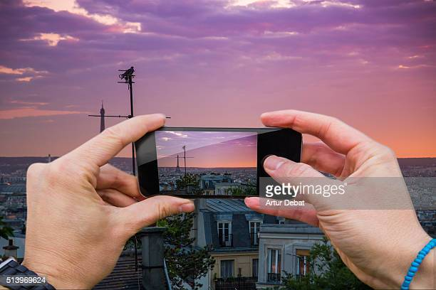 Man taking pictures from personal point of view with smartphone on top of Paris city with Tour Eiffel skyline on sunset.