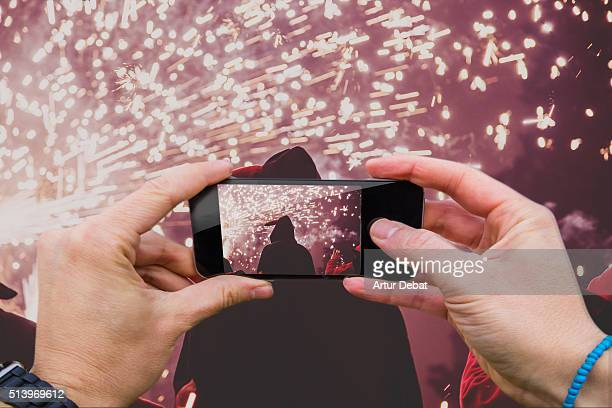 Man taking pictures from personal point of view with smartphone during the Catalan Correfocs at night with fire sparks.