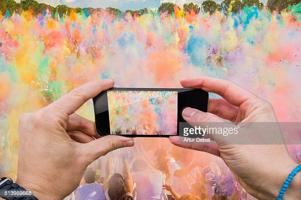 Man taking pictures from personal point of view with smartphone during the colorful celebration of the Holi festival with colorful powder.