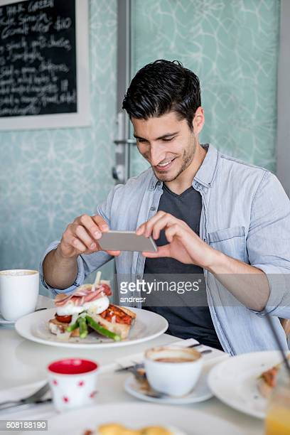 Man taking pictures of food at a restaurant