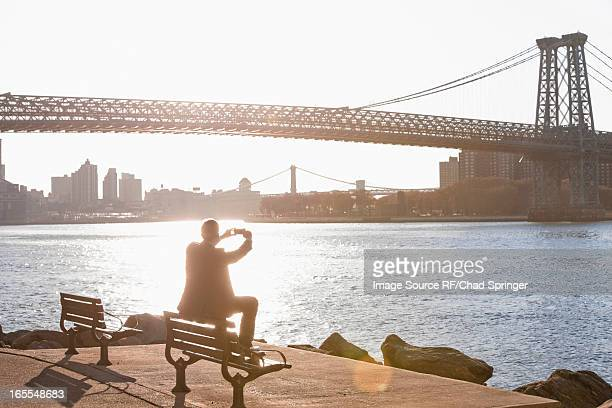 Man taking pictures of urban bridge