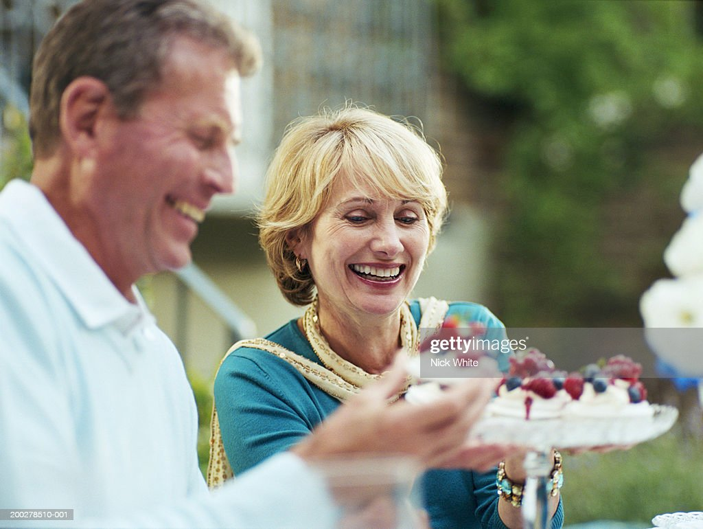 Man taking piece of cake from plate held by woman : Stock Photo