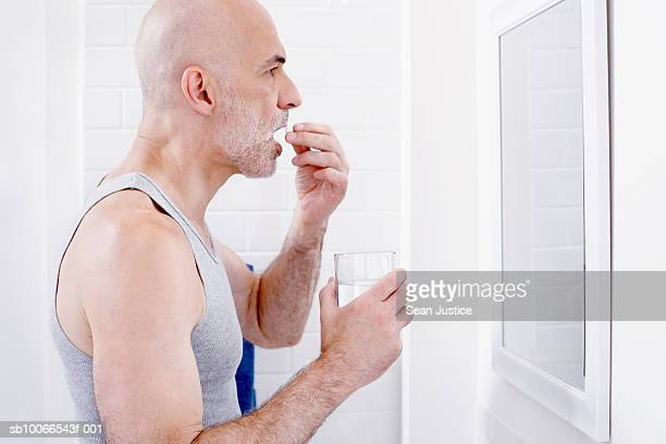 Man taking pills, looking in mirror in bathroom, profile