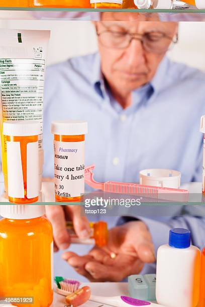 Man taking prescription pills out of medicine cabinet. Bottles, toiletries.