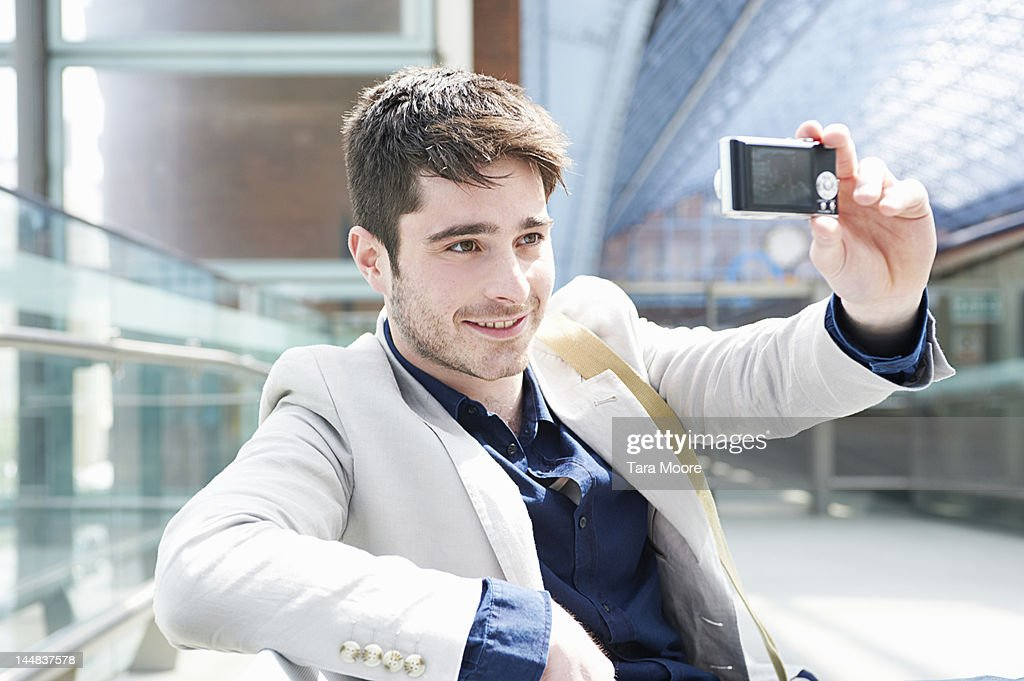 man taking self portrait with camera at station : Stock Photo
