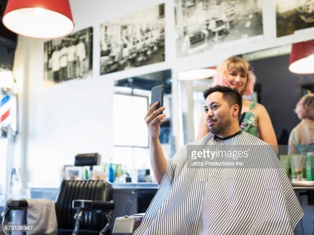 Man taking selfie after haircut in retro barbershop
