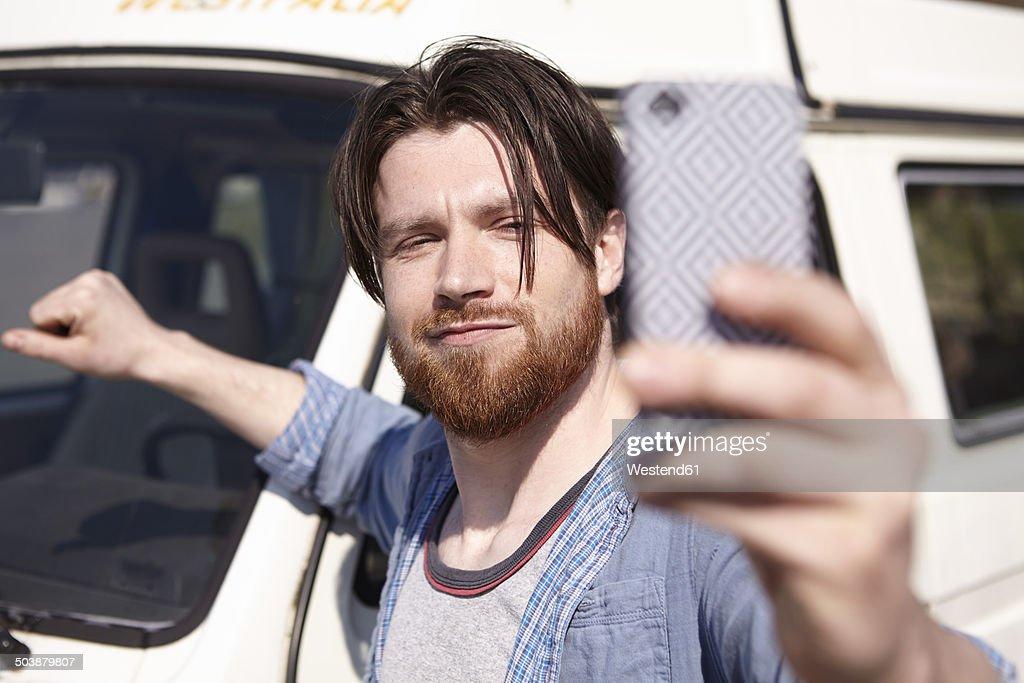 Man taking selfie in front of car