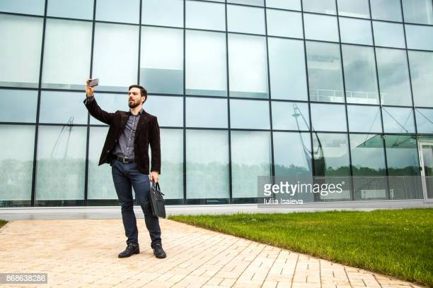 Man taking selfie near office building