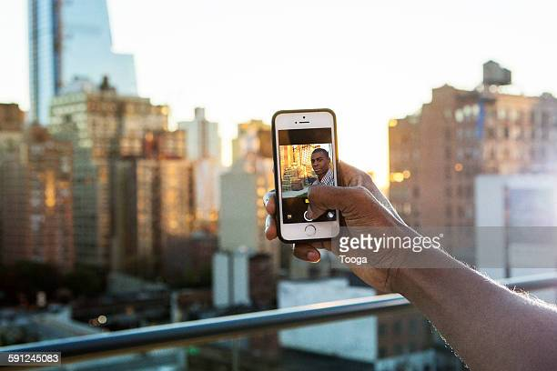 Man taking selfie on rooftop with cameraphone