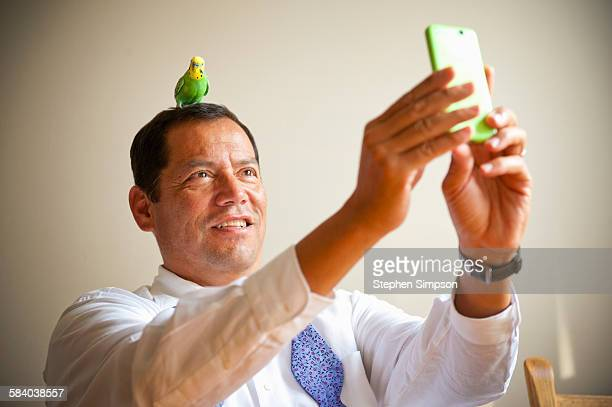man taking selfie with parrot on his head