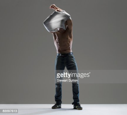 man taking shirt off : Foto de stock