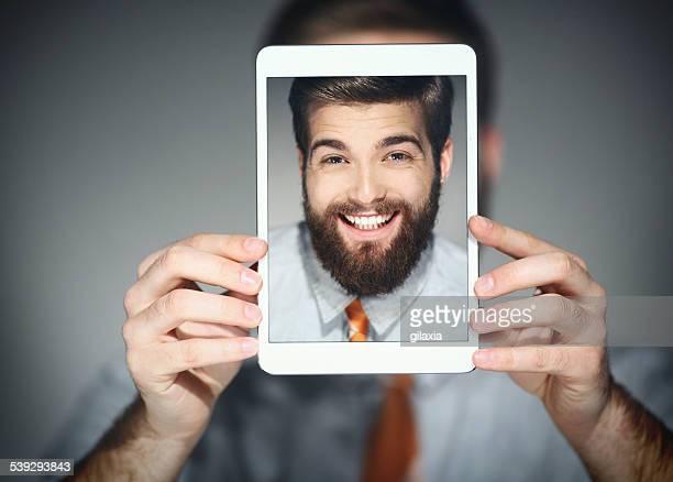 Souriant homme prenant selfie.