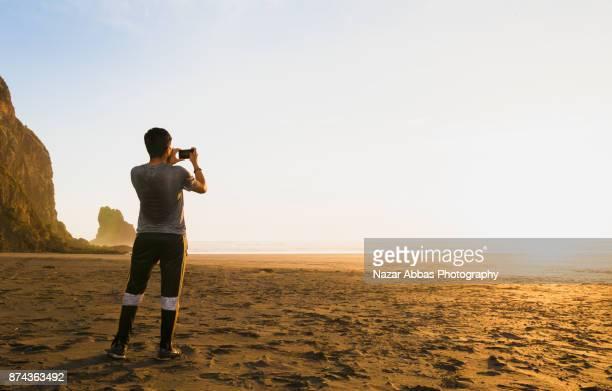 Man taking taking photo of sunset at Anawhata beach, Auckland, New Zealand.