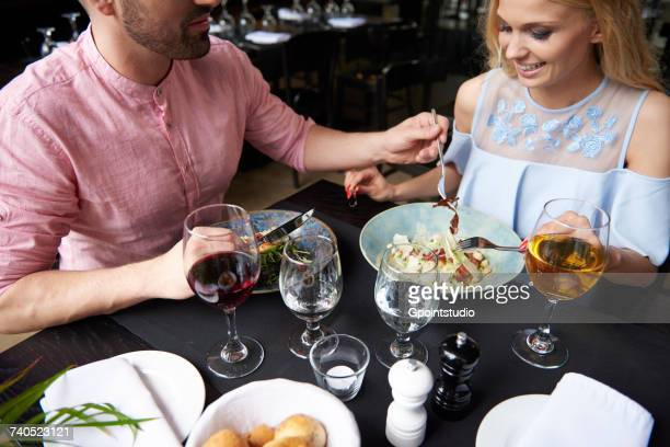 Man taking trying food girlfriends lunch at restaurant table