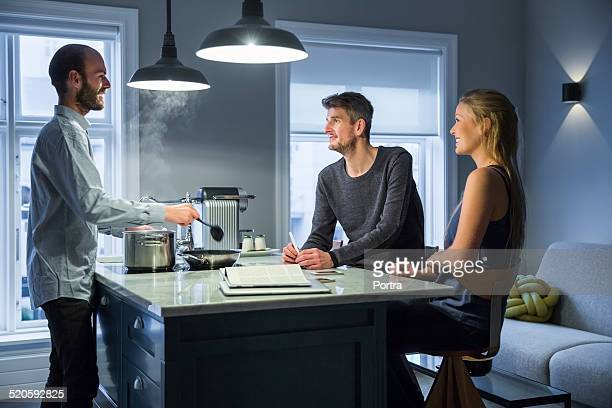 Man taking with friends while cooking in kitchen
