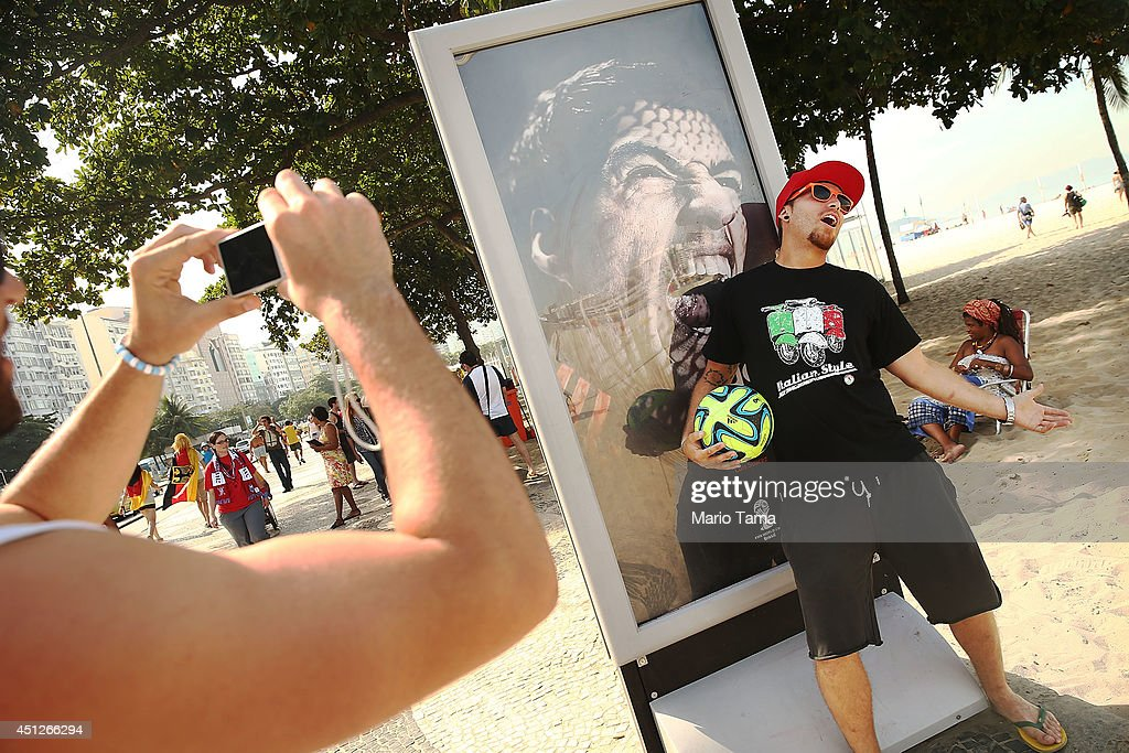 A man taks a photo next to an advertisement featuring Uruguay's Luis Suarez, mocking the biting incident against opponent Giorgio Chiellini during the World Cup match against Italy, on Copacabana Beach on June 26, 2014 in Rio de Janeiro, Brazil. Suarez has been banned in today's ruling by FIFA for four months.