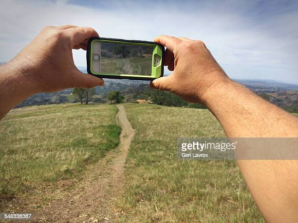 Man talking a picture of a footpath in nature using a smartphone