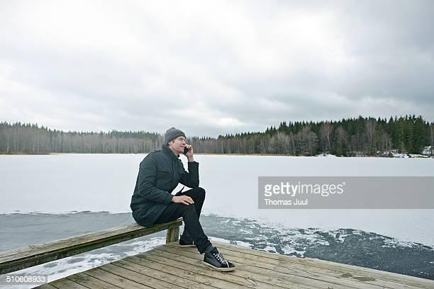 Man talking in phone by lake