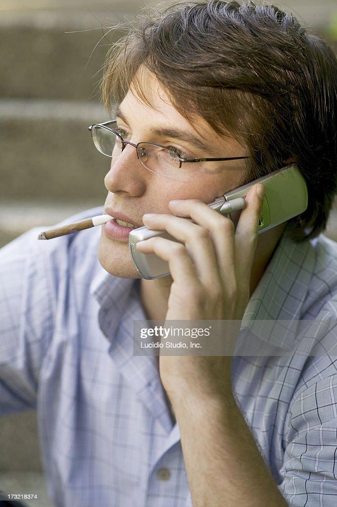 Man talking on a cellphone smoking a cigar