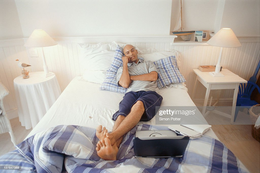 Man talking on cell phone in bed stock photo getty images for Cell phone bed