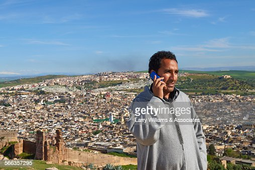 Man talking on cell phone over Fes cityscape, Fes-Boulemane, Morocco