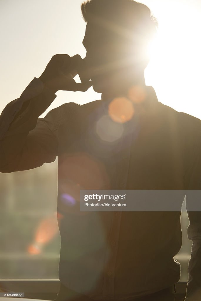 Man talking on cell phone, silhouetted by sun shining through window