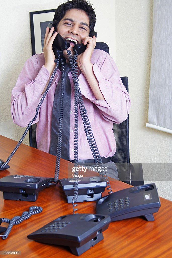 Man talking on many phones : Stock Photo